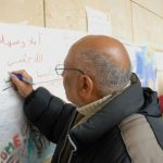 """Ibrahim Salim - who fled Baghdad with his daughters, son and their four small children - writes a message of thanks on the wall at Westbahnhof. """"This is the first time we have been shown any humanity since we left Iraq"""", he said. Photo: Kim Traill"""
