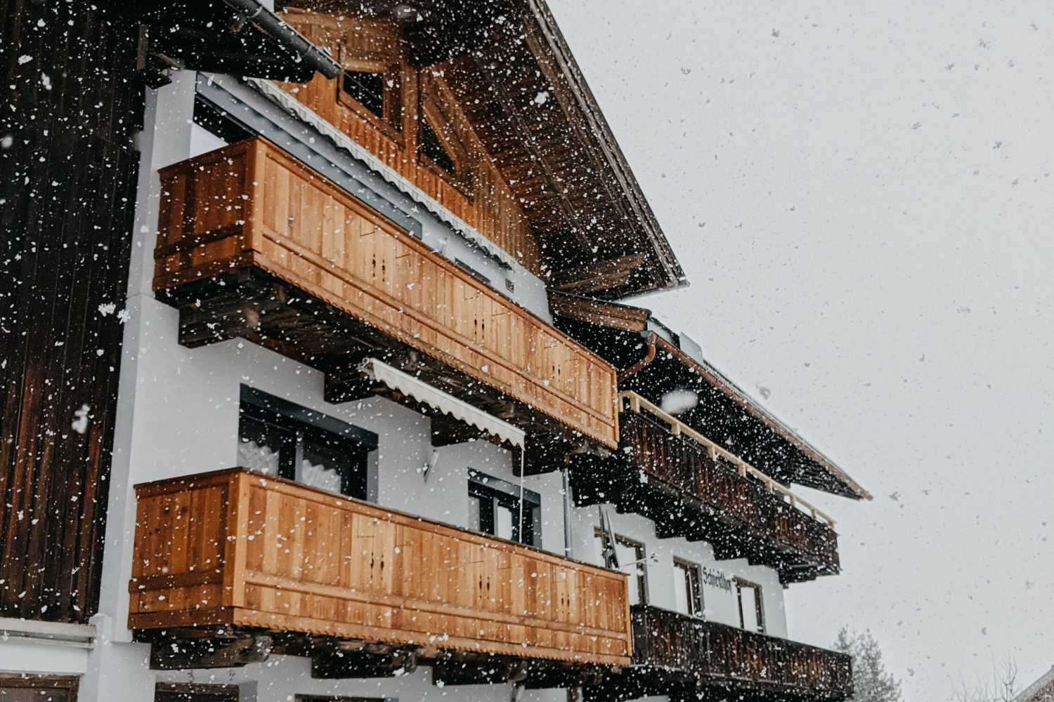 A wooden panelled Austrian home is kissed by petite snowflakes on a cosy day. Photo by Jara from Pexels