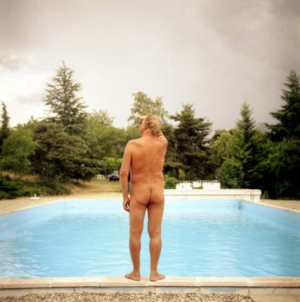 A naked man stands on the ledge of a pool. Photo by FRED DUFOUR / AFP