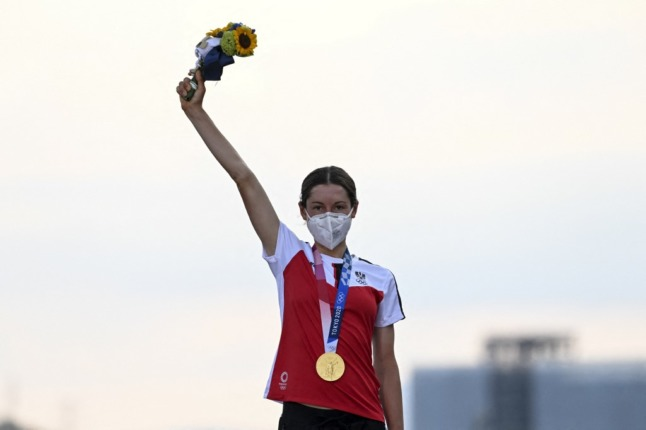 Austrian Gold medallist Austria's Anna Kiesenhofer celebrates on the podium during the medal ceremony for the women's cycling road race of the Tokyo 2020 Olympic Games (Photo by Greg Baker / AFP)