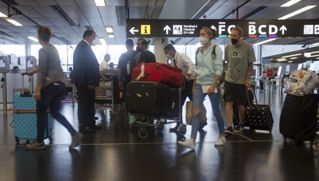 A third of Covid-19 infections come from travel. Passengers wear protective masks at the Vienna International Airport. (Photo by ALEX HALADA / AFP)