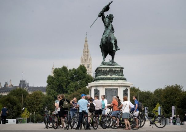 A group of tourists with bicycles outside the Hofburg palace at Heldenplatz (Heroes square) where Austria's new chancellor will be sworn in on Monday.