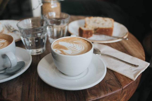 Several coffee cups sit next to a plate with cakes at a coffee house in Vienna. Photo by Alisa Anton on Unsplash